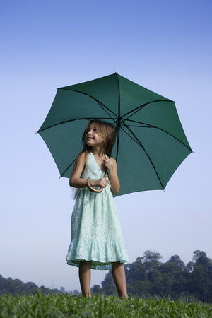 young girl with bright green umbrella Stock Photo
