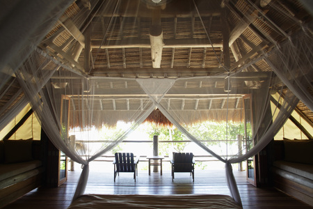 interior of thatched and wood house with mosquito netting