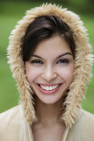 head shot of smiling young woman wearing fur hood.