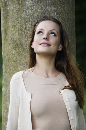 only young women: Portrait of woman leaning against tree looking up. LANG_EVOIMAGES