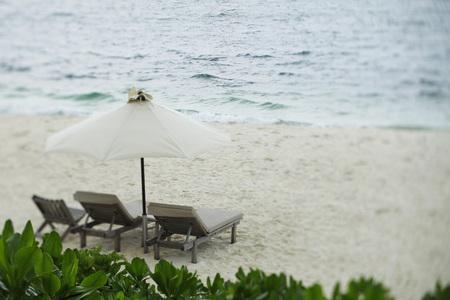 wooden lounge chairs under umbrella on beach Stock Photo - 77280358