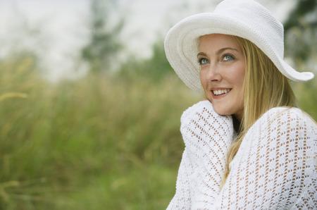 Blonde woman wearing white hat, eyes looking up