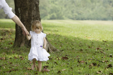 Little girl walking, holding womans hand Stock Photo