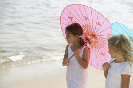 two girls walking on beach under umbrellas Banco de Imagens