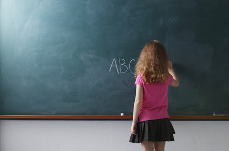 rear view of young girl writing on chalkboard Banco de Imagens