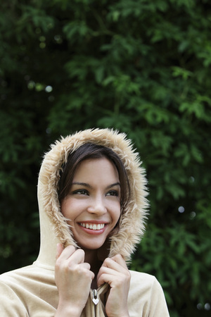 head shot of smiling young woman wearing hooded jacket.