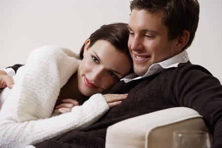 european ethnicity: young couple holding eachother on couch LANG_EVOIMAGES