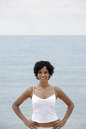 mujer mirando el horizonte: mujer sonriendo con las manos en las caderas, afuera