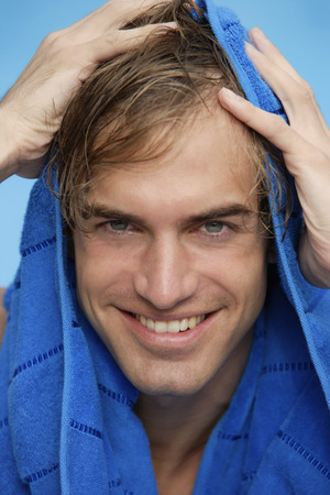 toweling: portrait of young man with blue towel on head