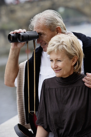 european ethnicity: mature man looking through binoculars with woman looking at view