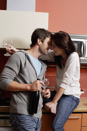 european ethnicity: young couple kissing and holding wine glasses