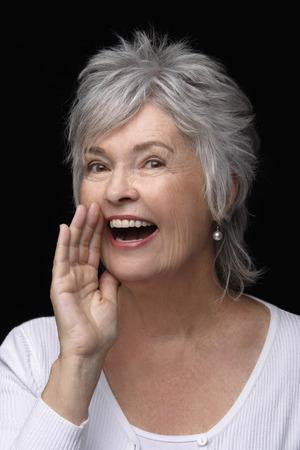 Oudere vrouw die een geheim vertelt.