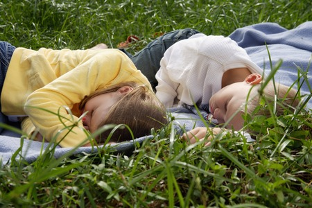 tiredness: brother and sister lying on blanket in park LANG_EVOIMAGES