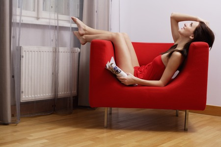 european ethnicity: young woman wearing red underwear relaxing in red chair LANG_EVOIMAGES