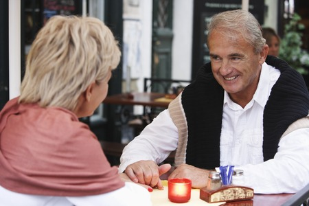 european ethnicity: mature couple having a candle lit dinner