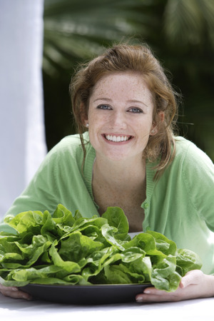 Young woman with plate of fresh lettuce