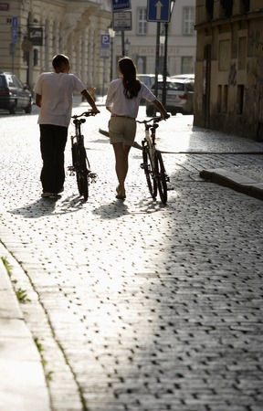 european ethnicity: young couple walking bikes down cobbled street