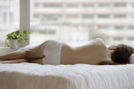 think through: young woman lying on her side on bed LANG_EVOIMAGES
