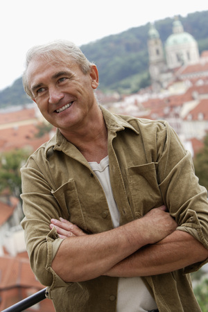 european ethnicity: mature man folding his arms and smiling with city as background