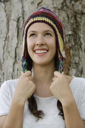 Teen girl wearing hat, leaning on tree