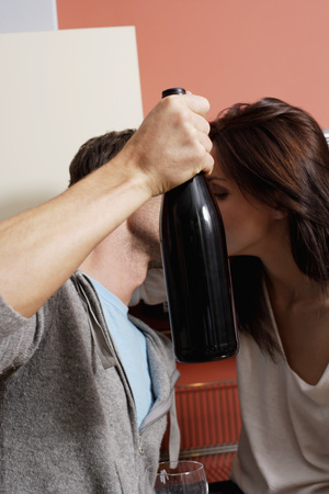 european ethnicity: young couple kissing behind wine bottle