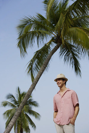 Man standing under palm trees Stock Photo