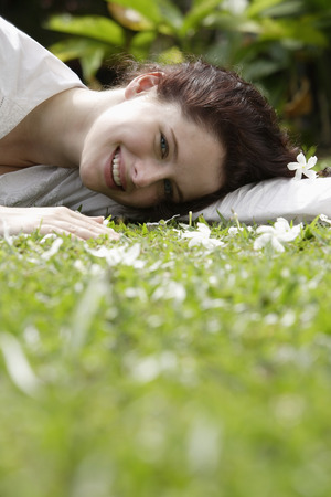 Woman on grass with white blossoms