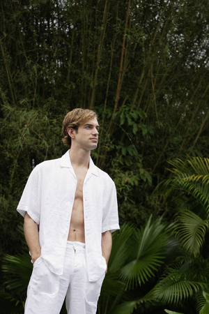 fully unbuttoned: portrait of young man wearing all white LANG_EVOIMAGES