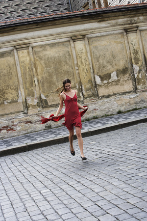 european ethnicity: young woman running across street in red dress