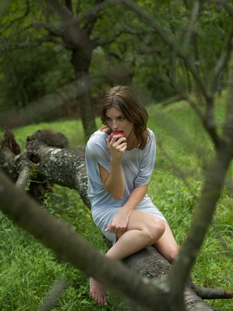 Young woman eating apple in woods