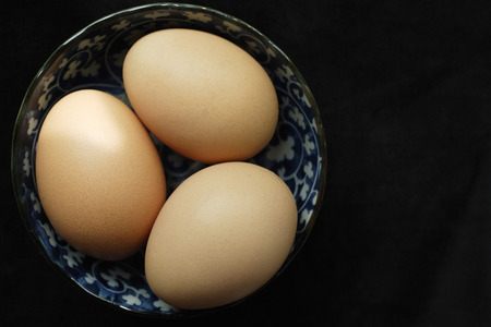 Three brown eggs in blue patterned bowl