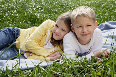 brother and sister lying on blanket in park LANG_EVOIMAGES