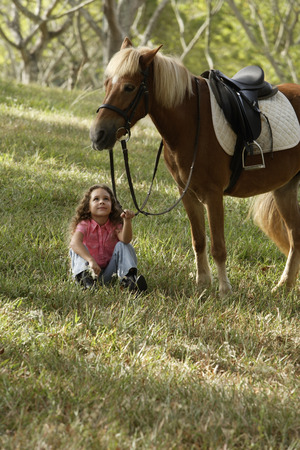 Young girl sitting under pony, holding reigns LANG_EVOIMAGES