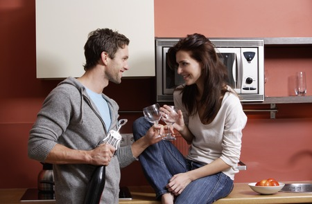 european ethnicity: young couple in kitchen holding wine glasses and smiling LANG_EVOIMAGES