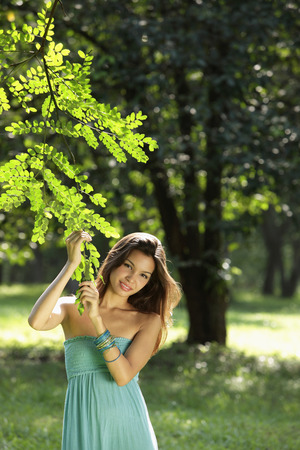 young woman holding leaves of tree and smiling