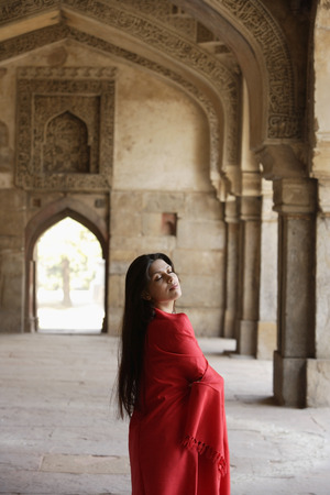 Woman in red shawl, standing in ancient monument Stock Photo - 77280459