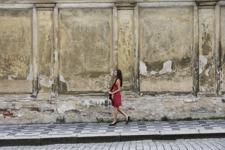 european ethnicity: young woman walking down the street in a red dress