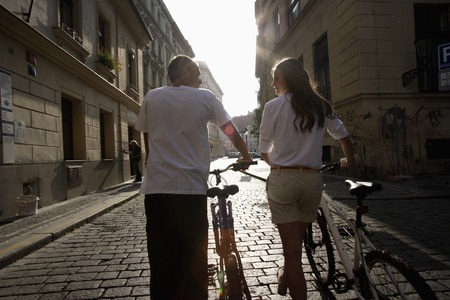 european ethnicity: young couple walking bicycles down cobbled stone street