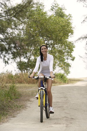 road cycling: young woman riding bike LANG_EVOIMAGES