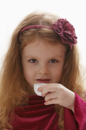 girl with gray eyes: Head shot of young girl holding tea cup