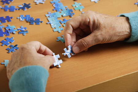 Close up of woman doing puzzle.