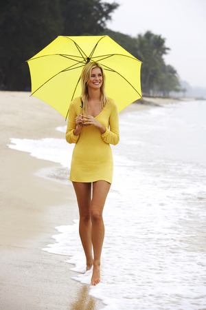 ankle deep in water: woman walking on beach with yellow umbrella LANG_EVOIMAGES