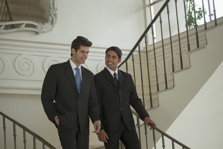 India, Two businessmen walking down stairs and talking