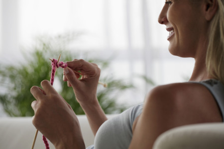 woman profile: profile of woman knitting and smiling LANG_EVOIMAGES