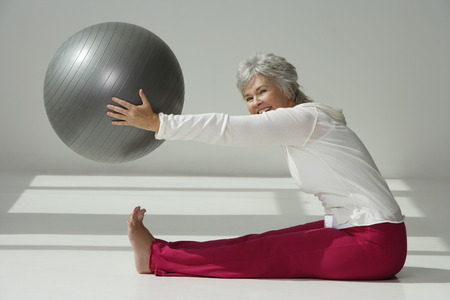 the well groomed: Mature woman stretching with exercise ball.
