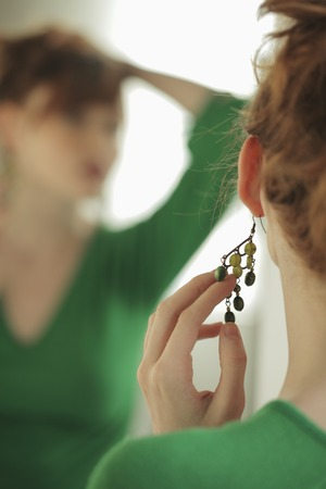 Rearview of young woman playing with her earring Stock Photo