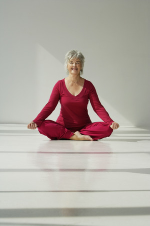Mature woman smiling while doing yoga. Stock Photo