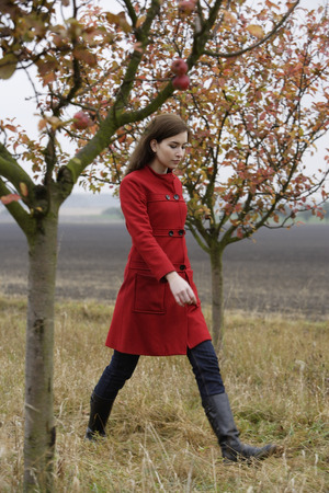 young woman walking through apple orchard