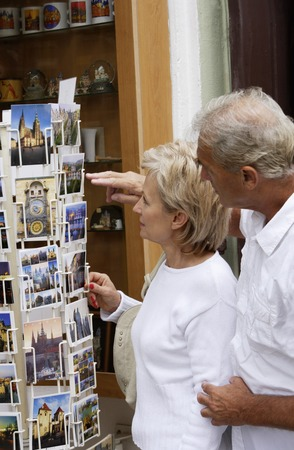 european ethnicity: mature couple looking at postcards
