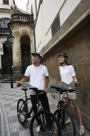 european ethnicity: young couple with bicycles holding map and looking up